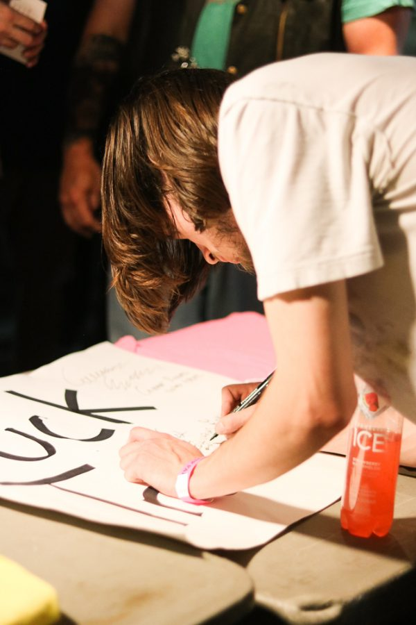 Logan Bush of Kill Vargas signs a fans poster at Riverfest on Thursday, June 6.