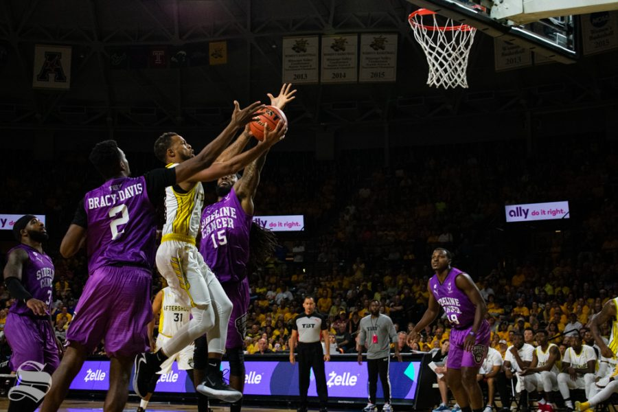 Sideline Cancer's Kevin Bracy-Davis and Aron Nwankwo reach to block the ball as Aftershocks' Clevin Hannah jumps for the basket during their game on July 27.