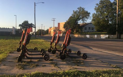 A fleet of e-scooters sit in an empty lot at 17th and Hillside near Wichita State's main campus. E-scooters are currently not allowed on campus.