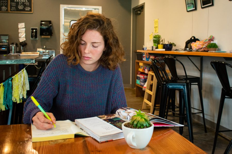 Morgan Cusick highlights sections of a book while she studies at Fairmount Coffee on August 8.