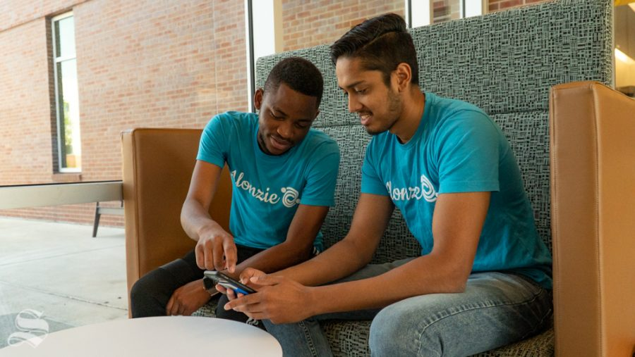 James Meli (left) and Zeeshan Khan check the Alonzie application for events. Meli is an undergraduate student majoring in computer engineering. Khan is a graduate student in the Masters of innovation and design program.