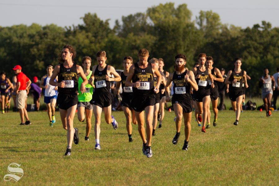 Wichita State men's cross country team jogs out onto the field to meet with their coach. Together the men's and women's teams swept the JK Gold Classic on Sept. 7 at 4 Mile Creek Resort.