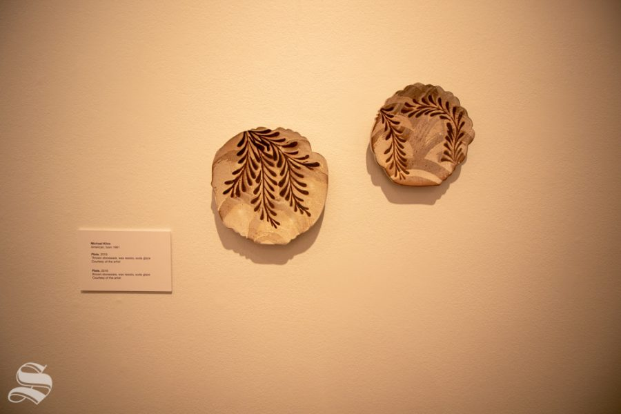 Micheal Klines pieces reside on a wall for display in the Ulrich on Sept. 12 for the museums Fall opeining event. The pieces were made from thrown stoneware, wax resists and soda Glaze.