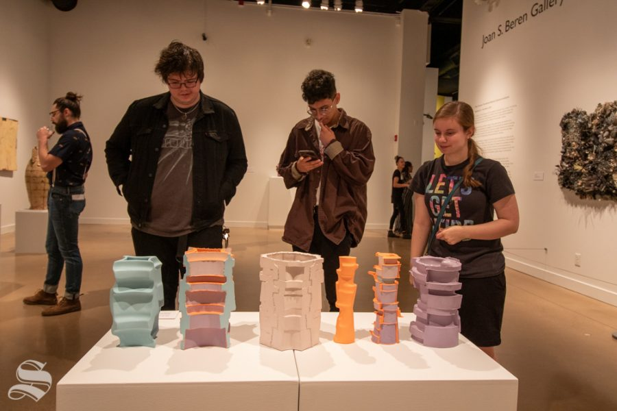 Jaedon Gray, Alfredo Aranda and Laura Barwick look at sculptures during the Ulrichs Fall opening event on Sept. 12.