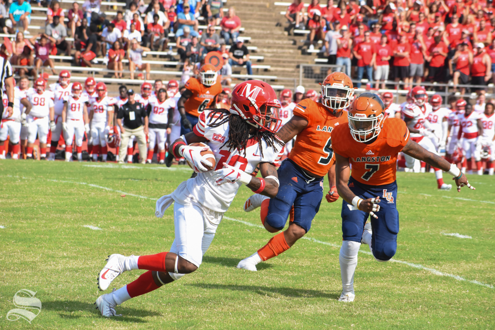 Eman McNeal, a senior tight end for the Bulldogs, runs the ball to the end zone while senior James Cox, a linebacker, and junior Quante Hayden, a defensive back, move to tackle. The game between the McPherson Bulldogs and the Langston Lions took place on Sept. 7 at Cessna Stadium.