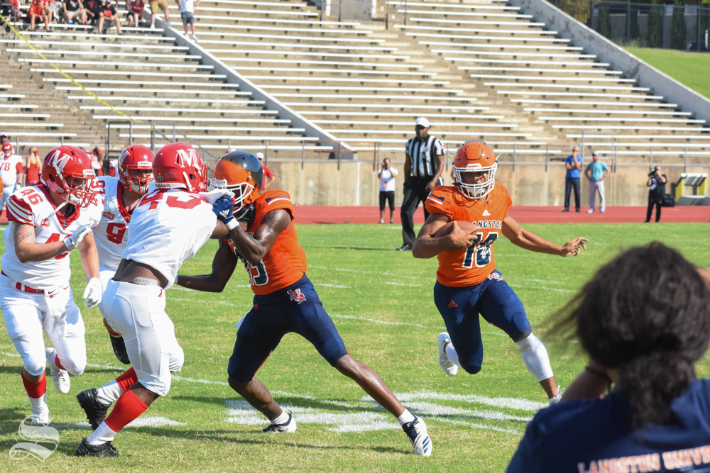 Freshman quarterback, Jordan Cooper, runs the ball around defenders during the first quarter of the game against the Bulldogs.