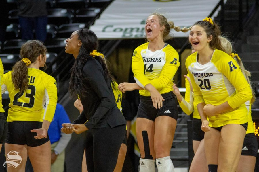 The Wichita State bench celebrates after winning the first set during the team's home opener against BYU on Thursday inside of Charles Koch Arena.