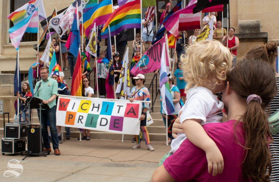 Two+children+watch+as+State+Rep.+Brandon+Woodard+speaks+outside+the+Sedgwick+County+Historic+Courthouse+at+the+2019+Wichita+Pride+Parade.+He+was+the+first+openly+gay+man+elected+to+the+Kansas+government.