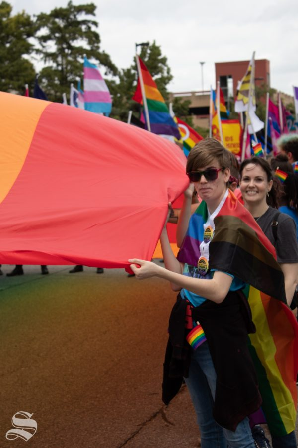 A parade participant holds one corner of an LGBT+ pride flag that was used in the 2019 Wichita Pride Parade. It immediately followed a United States flag.