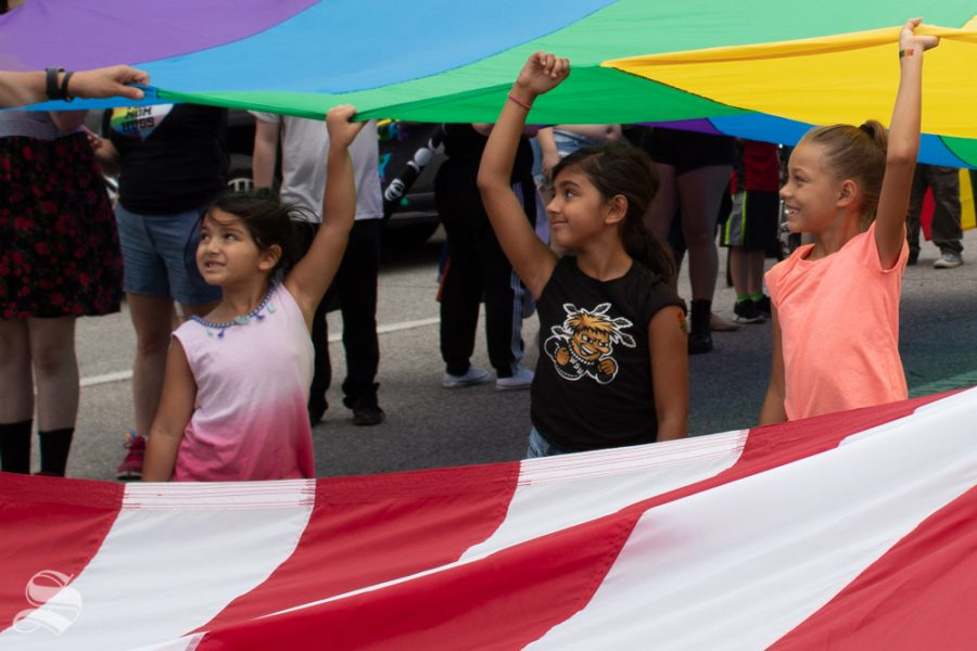 Three young parade participants hold part of an LGBT+ pride flag that was used in the 2019 Wichita Pride Parade. It immediately followed a United States flag.