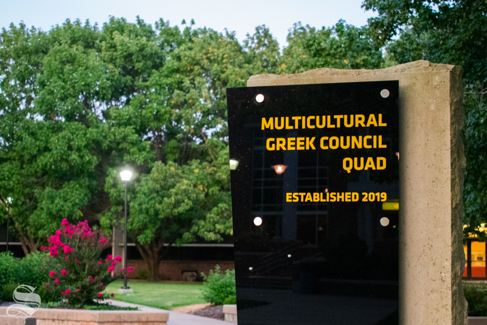 The Multicultural Greek Council Quad sign stands tall at the west entrance to the quad. The quad features cement pillars representing most of the MGC groups on campus.