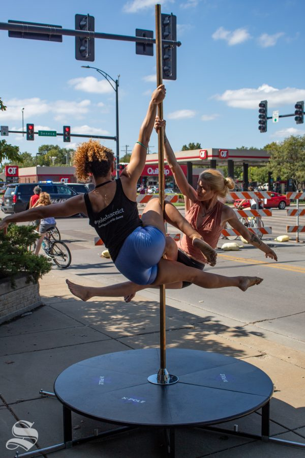Rebecca Ligget, left, and Ariel Larson display their pole-dancing skills Sunday at Open Streets ICT. The two help provide lessons at the nearby Sway Ballroom and Latin Dance Studio.