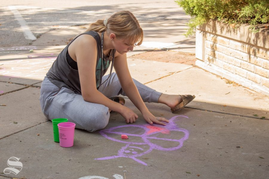 Taylah Corsiglin draws a chalk butterfly on the sidewalk at Open Streets ICT. Attendees were encouraged to