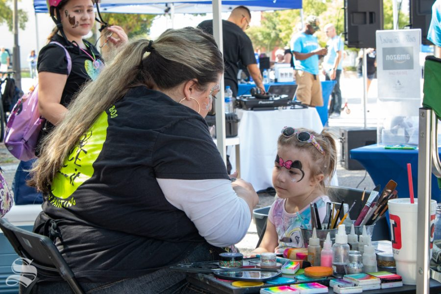 Kellsey Molina, left, paints a Minnie-Mouse design on Avery Roe's face Sunday at Open Streets ICT. Molina was one of four artists painting faces with Face-It Studios.