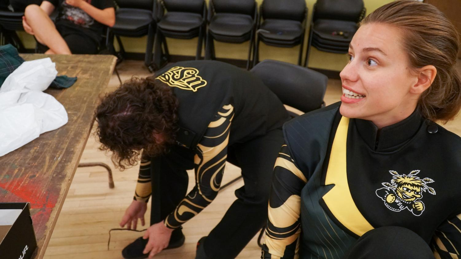 Sean Matson (left) and Katelyn Koch try on Shocker Sound Machine uniforms. Though she's not a music major, Koch says it's nice to continue playing her instrument after high school.