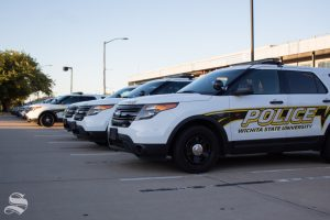 A line of Wichita State University Police Department patrol cars line department's parking lot off Perimeter Road.