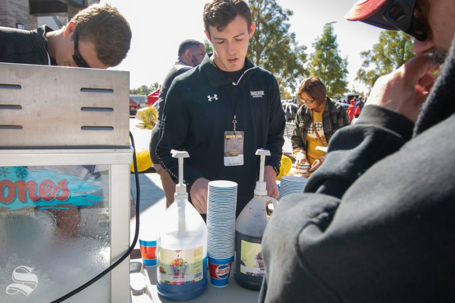 Jaxon Drake from Shocker Baseball serves snow cones with various flavors during the Trunk or Treat event on Saturday, Oct. 19 at Braeburn Square.