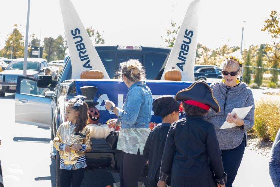 Airbus employees give candy and DIY paper airplanes to children during the Trunk or Treat event on Saturday, Oct. 19 at Braeburn Square.