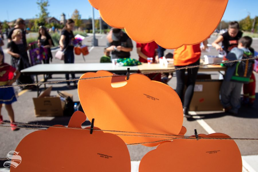 A wall of pumpkin crafts hang from strings near one of the tables during the Trunk or Treat event on Saturday, Oct. 19 at Braeburn Square.
