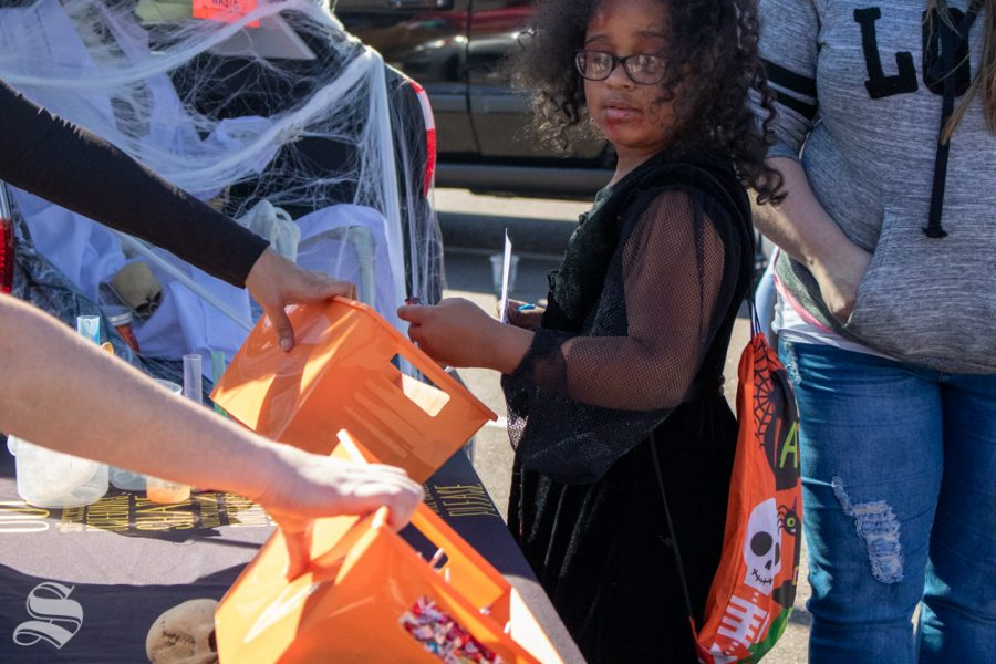 WSU Counseling and Testing Center employees hand out candy at the Trunk or Treat event on Saturday, Oct. 19 at Braeburn Square.