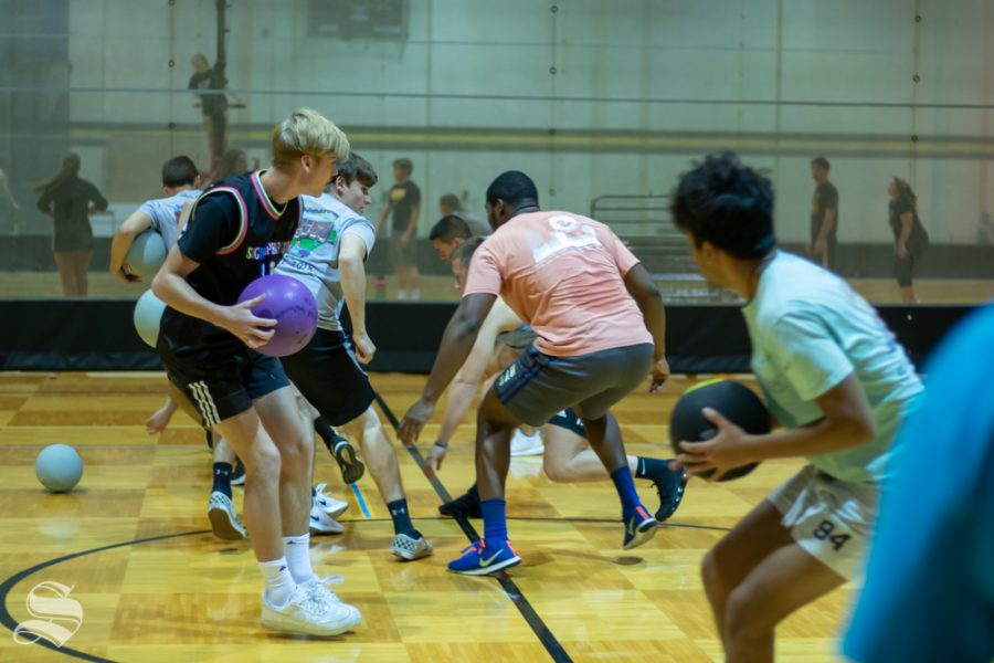 Sigma Alpha Epsilon and Sigma Phi Epsilon scramble to grab the dodgeballs at the beginning of the Dodgeball Tournament on Wednesday, Oct. 23 at the Heskett Center Gym.