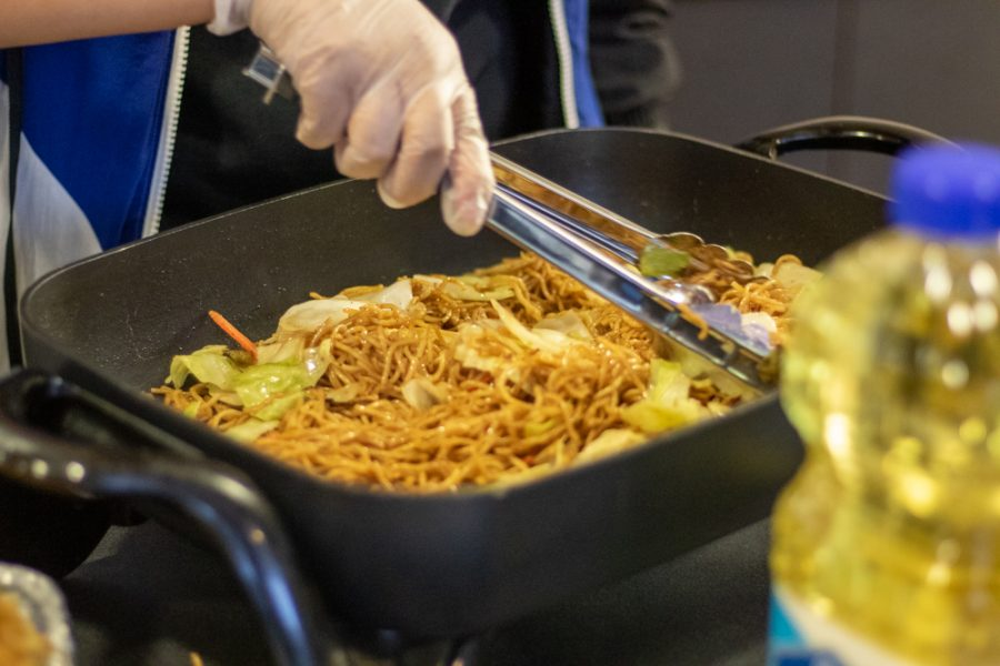 Micah Parga cooks a noodle dish at the Japanese table during Interfest on Oct. 3 in Hubbard Hall. The event was moved from the Multicultural Greek Council Quad to Hubbard Hall due to weather.
