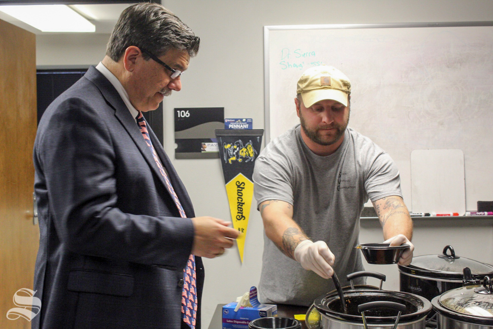 Student Veterans Organization member Drew Edwards, right, serves chili to aerospace professor Tony Vizzini Friday at the SVO's annual chili cook-off. The event moved indoors ahead of an incoming storm.