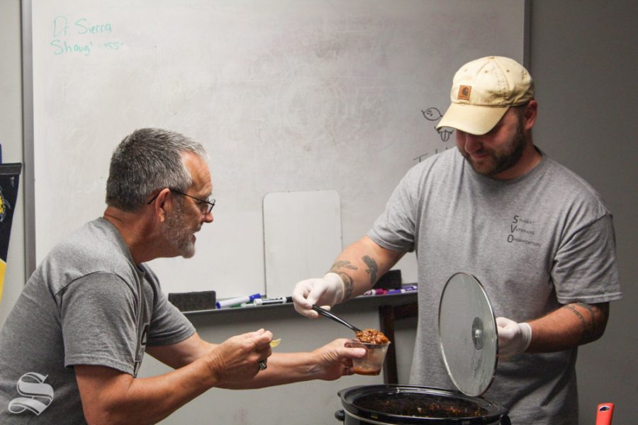 Student Veterans Organization member Drew Edwards, right, serves chili to Dan Bogle Friday at the SVO's annual chili cook-off. The event moved indoors ahead of an incoming storm.