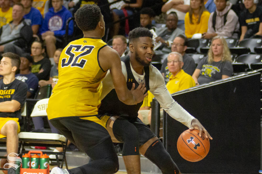 Sophomore guard Jamarius Burton dribbles past freshman Grant Sherfield during the Black and Yellow Scrimmage on Saturday inside Charles Koch Arena.