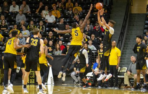 Wichita State sophomore Dexter Dennis attempts a three-pointer before the final buzzer over junior Trey Wade on Saturday during the Black and Yellow Scrimmage inside Charles Koch Arena. Wade ended up blocking the shot, securing a win for the Yellow Team.