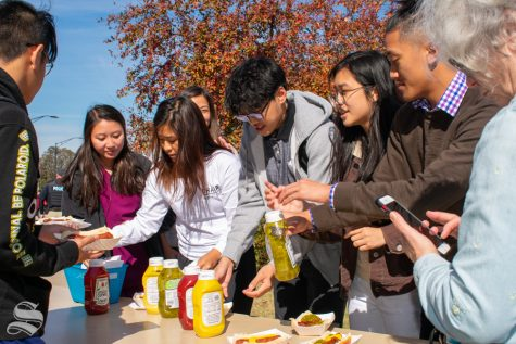 Wichita State students line up at the condiment table after getting their hot dogs during the Pop-up Picnic on Wednesday, Oct. 23 at the Duerksen Fine Arts Amphitheater.