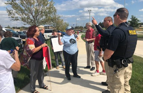Protesters argue with officers about if they have to move from in front of the Law Enforcement Training Center ahead of Attorney General Bill Barr