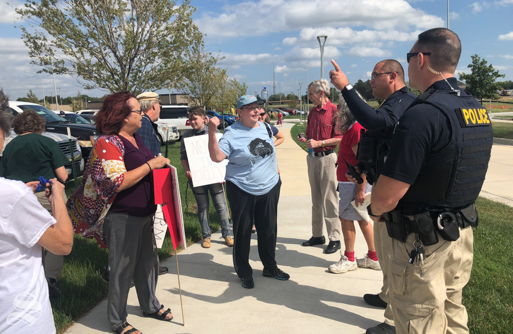 Protesters argue with officers about if they have to move from in front of the Law Enforcement Training Center ahead of the attorney genera;'s visit. They were ultimately allowed to stay.