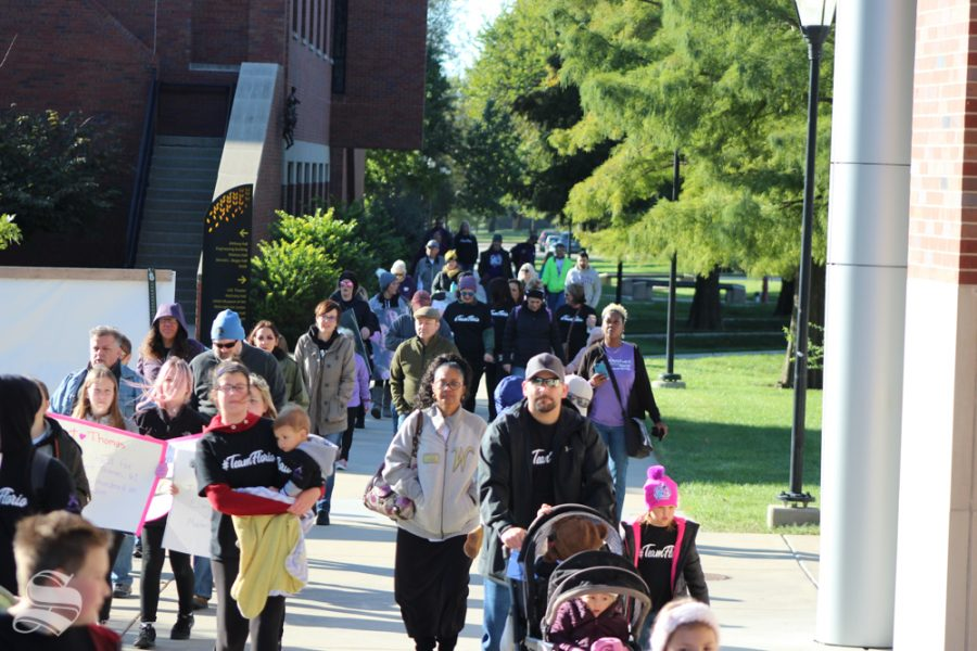 Children, families and other participants walk the last stretch of the Purple Mile during the event on Saturday, Oct. 12, on Wichita States main campus. The Purple Mile event brings awareness of the effect of domestic violence.