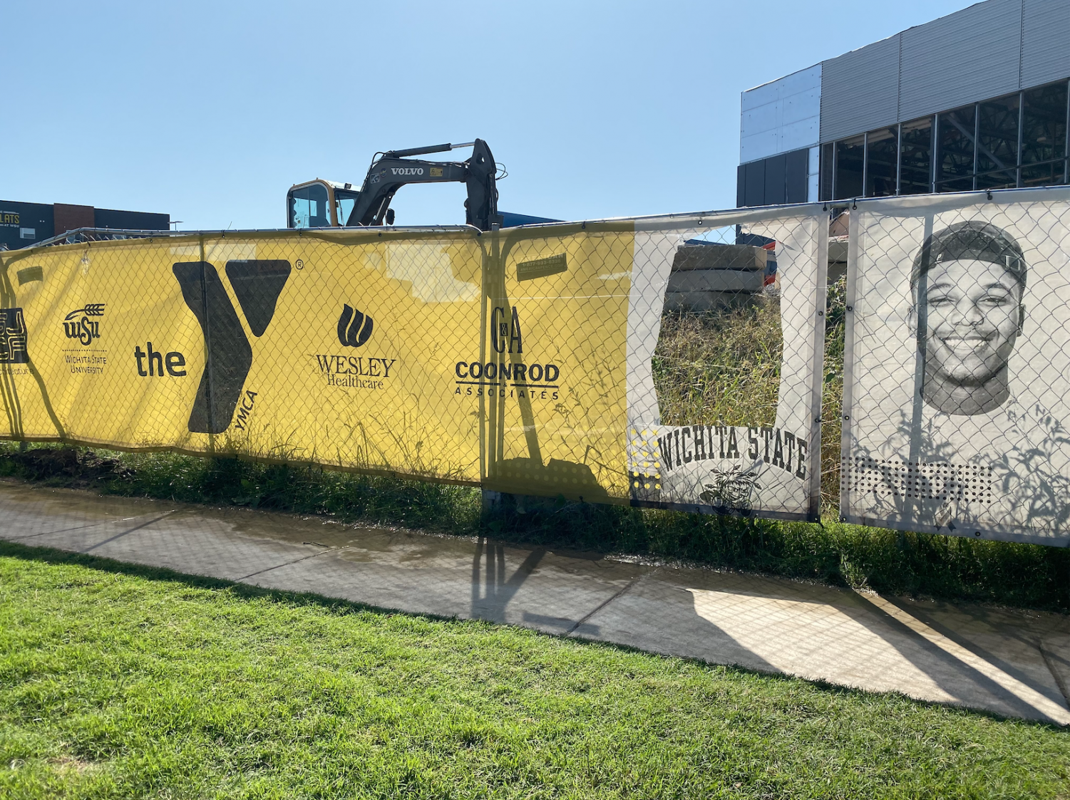 A person's face was cut out of a banner hanging outside the construction site of the soon-to-be Steve Clark YMCA and Student Wellness Center.
