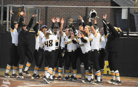 Wichita State teammates cheer for freshman Kiersten Nixon after she hit a home run during the game against Cowley Community College on Oct. 21. The Shockers defeated the Tigers 21-1.