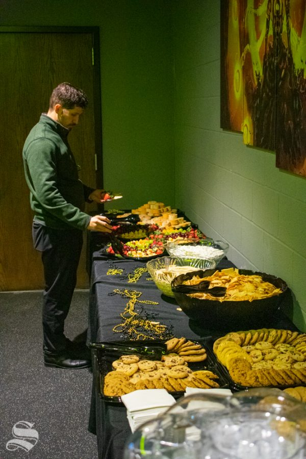Kegan Clark, an academic advisor and tutor coordinator with TRIO Disability Support Services, grabs snacks from the provided selection during the opening of the WSU esports hub on Tuesday, Nov. 5 in the Heskett Center.