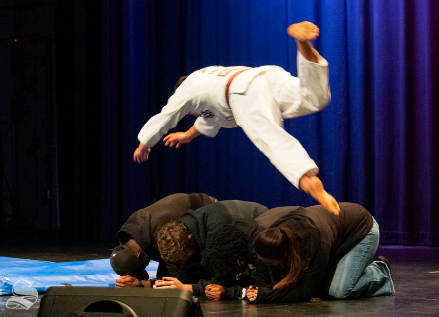 Audience members huddle together as Akishige Kuraishi dives over them during the Wichita State Judo Club demonstration at Yokoso: Japanese Culture Night on Friday, Nov. 1 in the CAC Theater.