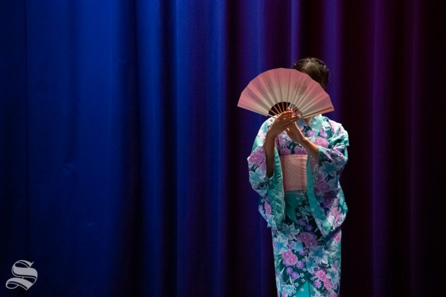 Freshman Marina Hata begins her performance of a traditional fan dance during Yokoso: Japanese Culture Night on Friday, Nov. 1 at the CAC Theater.