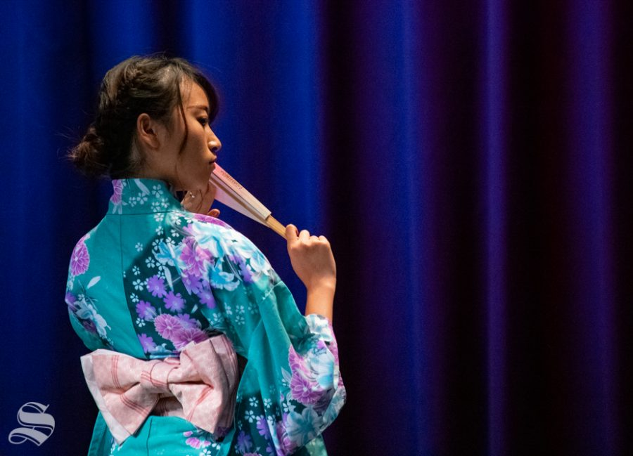 Freshman Marina Hata performs a traditional fan dance during Yokoso: Japanese Culture Night on Friday, Nov. 1 at the CAC Theater.