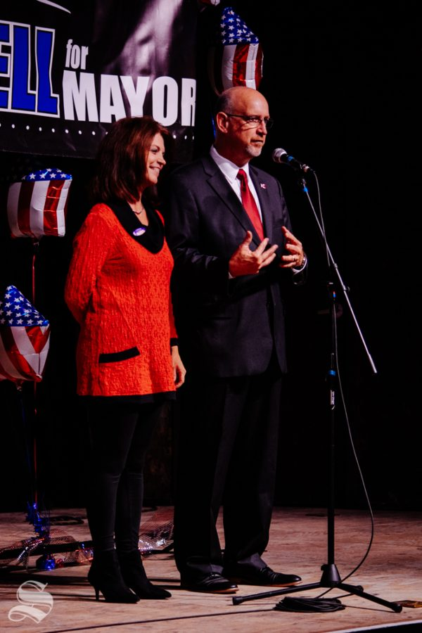 Susie Longwell stands with her husband Jeff while he addresses the crowd during the Longwell mayoral watch party on Tuesday, Nov. 5 at WAVE in downtown Wichita.