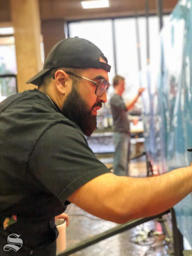 Wichita State senior and studio art major Bryan Raymundo draws different poses during Draw Surge in the McKnight Atrium on Monday December 2, 2019.