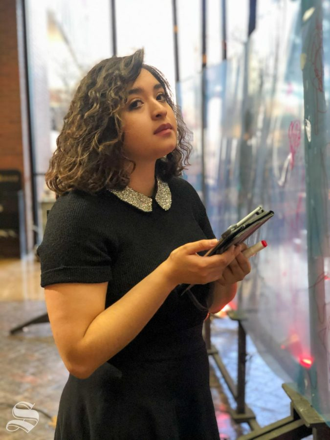 Graduate student and studio art major Lily Guillen controls the music during Draw Surge in the McKnight Atrium on Monday December 2, 2019.