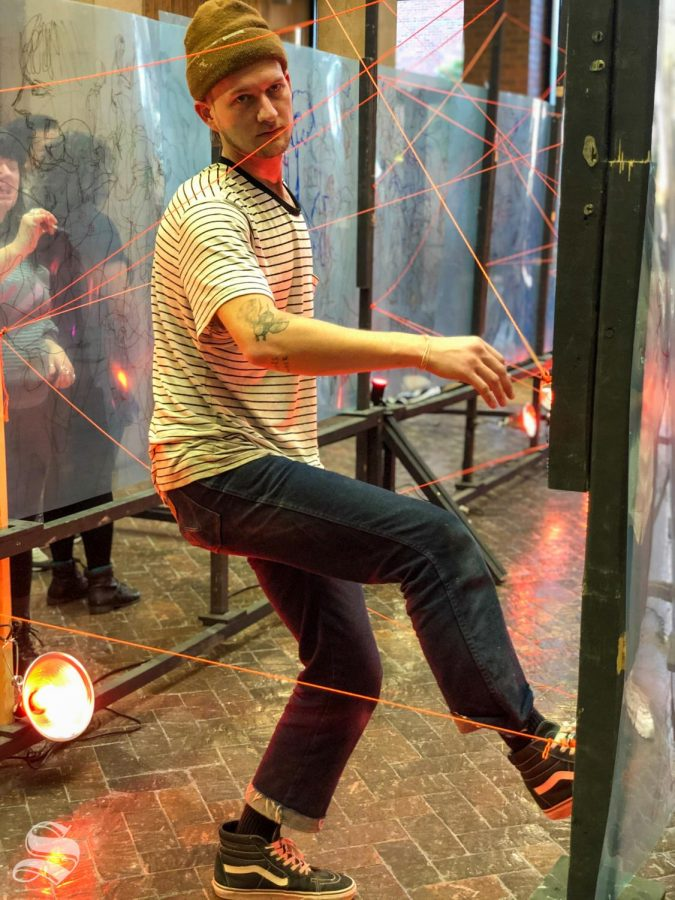 Grant Stuart going through the laser maze during Draw Surge. He was one of the many people who help set it up in the McKnight Atrium on Monday December 2, 2019.