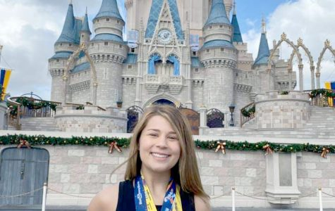 Madeline Shonka stands in front of the castle at Disney World with her medals from running a 5k, 10k, and half marathon for three consecutive days.