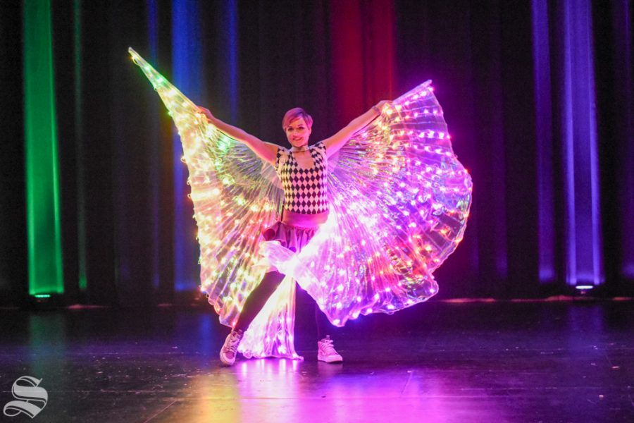 Kelsey Philo, a performer for Inspyral Circus, spins in a glowing dress during the Glow Circus on Monday inside the CAC Theater.