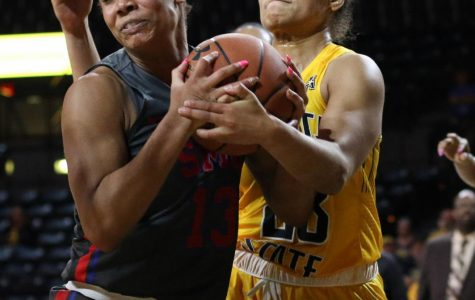 Southern Methodist's Reagan Bradley and Wichita State's Seraphine Bastin wrestle over a rebound during the game at Charles Koch Arena on Wednesday, Feb. 19, 2020.