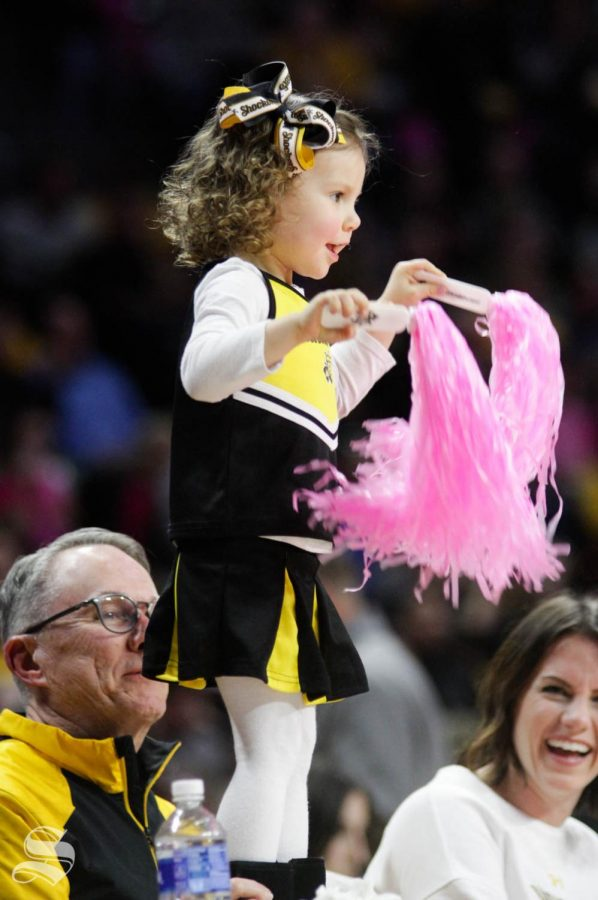 A young Wichita State fan stands on a table and cheers during a timeout during the game against USF on Feb. 20 inside Charles Koch Arena.