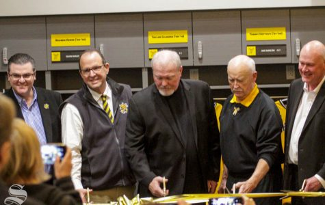 Wichita State Head Coach Eric Wedge cuts the grand opening ribbon on Friday inside the brand new baseball locker room.