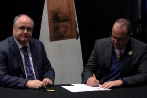 Wichita State President Jay Golden (right) and Lightning Divergent Systems President David Willmot sign an agreement between the university and LDS giving exclusive licensing of new technology that protects wind turbines from lightning strikes. The new technology will be tested further with the intent to commercialize the product.